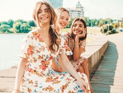 Three young beautiful smiling hipster girls in trendy summer sundress.Sexy carefree women posing on the street background. Positive models having fun and hugging. Sitting after shopping