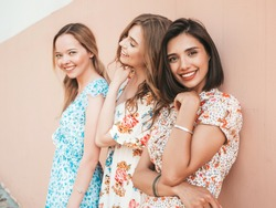Three young beautiful smiling hipster girls in trendy summer sundress.Sexy carefree women posing on the street near wall. Positive models having fun and hugging