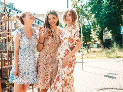 Three young beautiful smiling hipster girls in trendy summer sundress.Sexy carefree women posing on the street background.Models having fun and hugging.Discussing and walking after shopping
