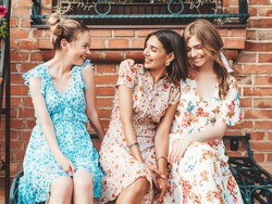 Three young beautiful smiling hipster girls in trendy summer sundress.Sexy carefree women posing on the street background.Models having fun and hugging. Sitting on the bench after shopping