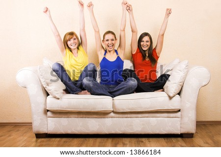 Three young beautiful women are cheering on a lounge