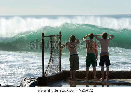 Three young boys checking out the surf.