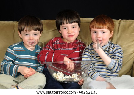 Three young boys watching a movie on television