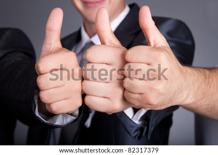 Three young business man  a thumb up sign