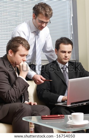 Three young business men working  together with laptop in the office