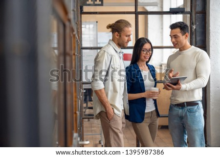 Three young business professionals standing together and discussing over business report in office hallway. Office colleagues revieving a business document on the tablet in coworking