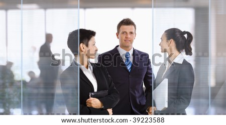 Three young businesspeople standing in modern office talking and smiling.