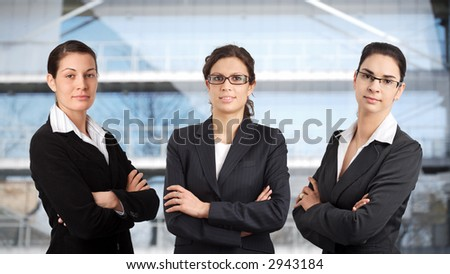 Three young businesswomen are posing in front of an office building.