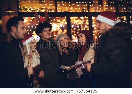 Three young cheerful couple having fun at the Christmas outdoor party in the city street at night and with a lot of lights on background.