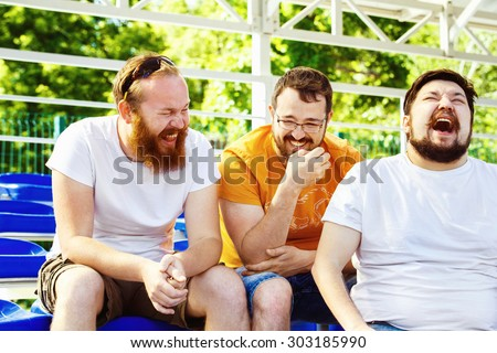 Three young cheerful friends are talking and laughing at summer day stadium background.