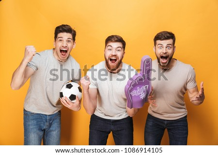 Three young cheery men football fans celebrating isolated over yellow background