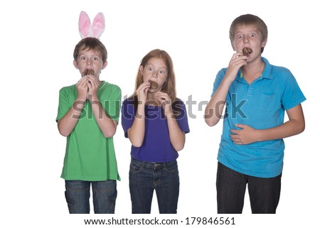 three young children eating and stuffing their mouths with marshmallow chocolate easter eggs