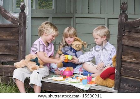 Three young children in shed playing tea and smiling