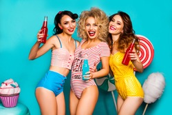 Three young cool lady on a turquoise background drink soda bottles, laughing, best friends, crazy emotions, Huge candy, lollipops, cotton candy, Cake, fashionable Pin-up girl, make-up and hairstyles