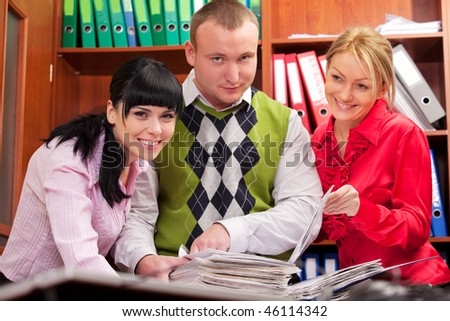 Three young coworkers doing paperwork - stock photo
