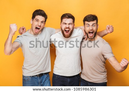 Three young excited men celebrating success together and screaming isolated over yellow background #1085986301