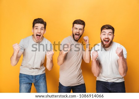 Three young excited men celebrating success together isolated over yellow background #1086914066