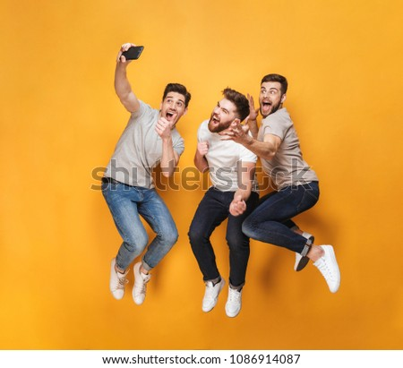 Three young excited men taking a selfie together while jumping isolated over yellow background #1086914087