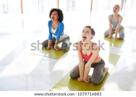Three young females in simhasana posture rolling their eyes and sticking out tongues on mats