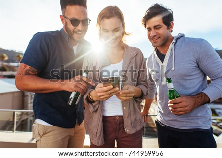 Three young friends at rooftop party looking at the smart phone together. Group of young men and woman standing and using mobile phone.