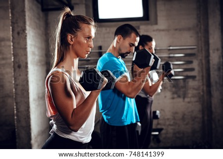 Three young friends doing exercise for bicep at the gym. Selective focus. Focus on girl, on foreground.