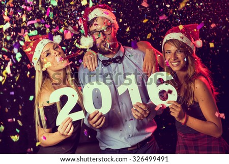 Three young friends having fun at New Year\'s Eve Party, holding cardboard numbers 2016