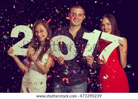Three young friends having fun at New Year\'s Eve Party, holding cardboard numbers 2017