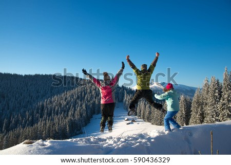 Three young friends jumping and having fun on the snowy mountains #590436329