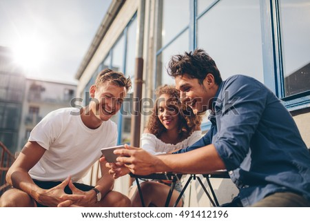 Shutterstock Three young friends sitting outdoors and looking at mobile phone. Group of people sitting at outdoor cafe and watching video on the smartphone.