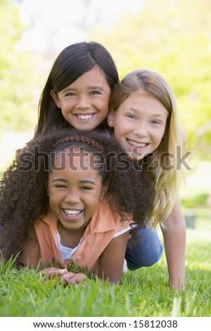 Three young girl friends piled up on top of each other outdoors smiling