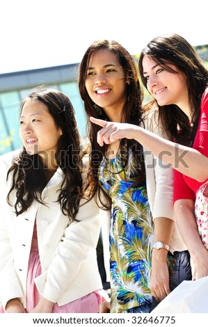 Three young girlfriends at outdoor mall pointing - stock photo
