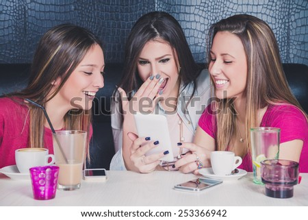Three young girls laughing while looking at the mobile phone in a cafe