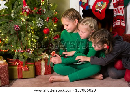 Three young girls looking at the presents under their christmas tree