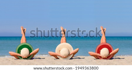 Three young girls on the beach wearing straw hats in the color of the flag of Italy. Ideal vacation concept in a resort in Italy. Focus on hats.