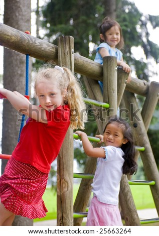 Three young girls playing in a playground. Diversity and friends