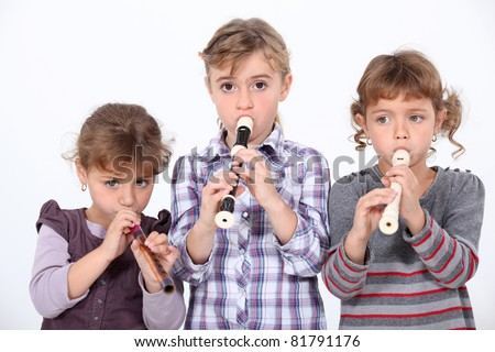 Three young girls playing the recorder
