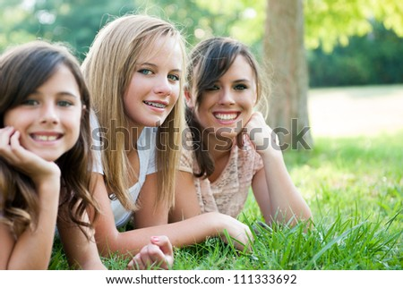 Three young girls/sisters sitting in the grass smiling