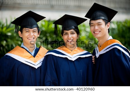 Three young graduates standing outdoors in graduate attire