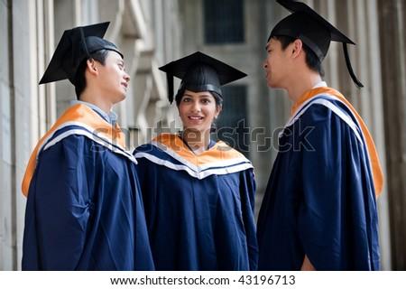 Three young graduates wearing graduation attire chatting in a hallway