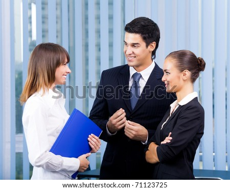 Three young happy businesspeople at office