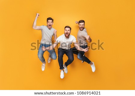 Three young happy men jumping together isolated over yellow background #1086914021