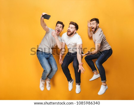 Three young happy men taking a selfie together while jumping isolated over yellow background #1085986340