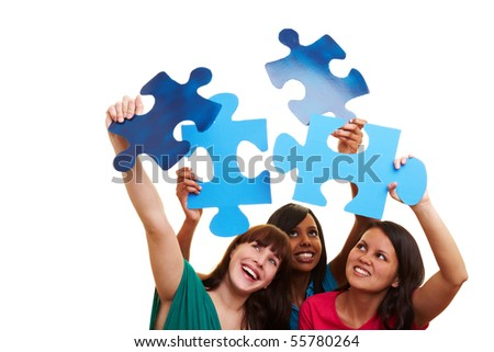 Three young happy women holding big jigsaw pieces