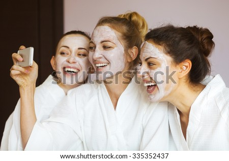 Three young happy women with face masks taking selfi at spa resort. Frenship and wellbeing concept #335352437