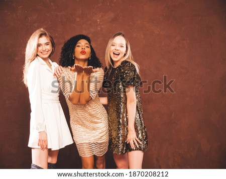 Three young international beautiful brunette women in trendy summer shiny dress.Sexy smiling carefree female posing  in studio.Fashionable models with bright evening makeup. Giving air kiss