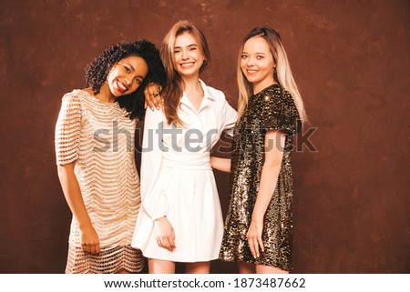Three young international beautiful brunette women in trendy summer shiny dress.Sexy smiling carefree female posing  in studio.Fashionable models with bright evening makeup