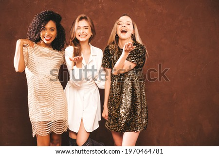 Three young international beautiful brunette women in trendy summer  shiny dress.Sexy smiling carefree female posing near blue wall in studio.Fashionable models with bright evening makeup