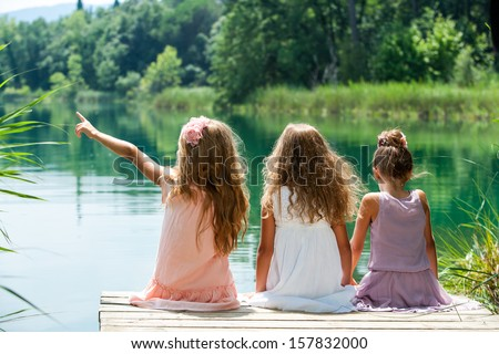Three young kids sitting together on jetty at lakeside.