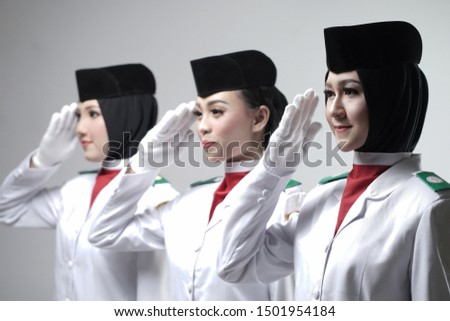 Three young lady Indonesian National Flag Hoisting Troop salutes isolated on white background.. National Paskibraka Council.
