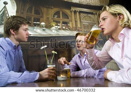 three young men drinking beer in a bar